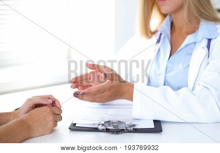 Doctor and patient are discussing something, just hands at the table.
