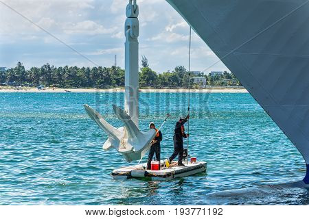 Toamasina Madagascar - December 22 2017: Two workers clean and make maintenance service to the anchor of a passenger ship moored at Toamasina Madagascar East Africa.