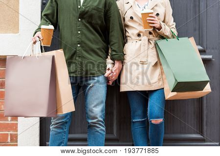 cropped shot of casual couple standing with shopping bags and drinking coffee on street