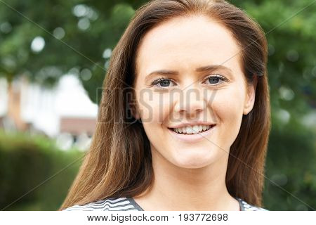 Outdoor Head And Shoulders Portrait Of Smiling Teenage Girl