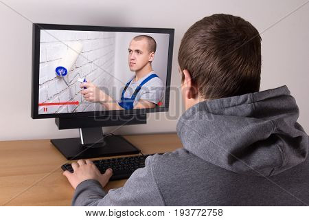 Young Man Watching Builder's Video Blog