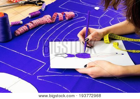 Workplace of a dressmaker: scissors pattern needles textile sewing spools and measuring tape. Girl drawing model wearing purple dress.