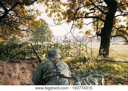 Unidentified Re-enactor Dressed As German Wehrmacht Infantry Soldier In World War II Hidden Sitting With Rifle Weapon In An Ambush In Trench In Autumn Forest