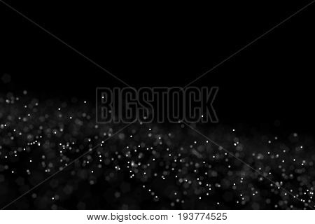 Freeze motion of white powder coming down, isolated on black, dark background. Abstract design of falling dust cloud. Particles cloud screen saver, wallpaper with copy space. Rain, snow fall