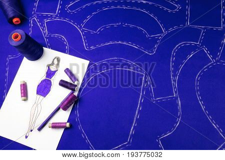 Workplace of a dressmaker: pattern textile sewing spools sketch and pencil.