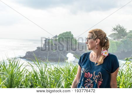 Woman on a background of Pura Tanah lot temple, Bali island.