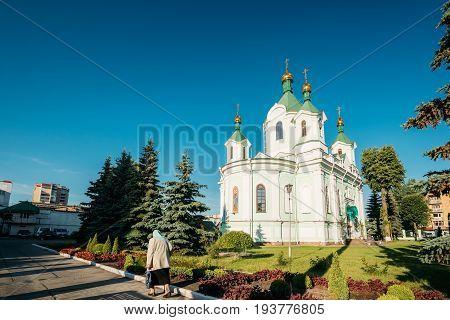 Brest, Belarus. Elderly Woman Walking Near Simeon's Stylites Cathedral Church.