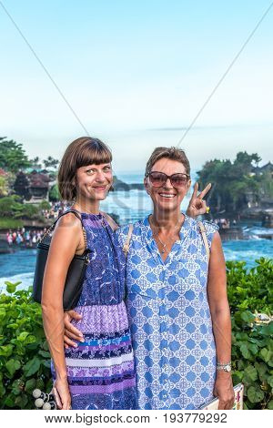 BALI, INDONESIA - MAY 4, 2017: Woman on a background of Pura Tanah lot temple, Bali island.