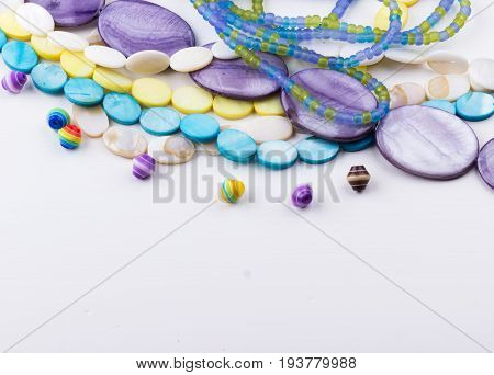 Glass and seed beads gemstone beads on white background. Selective focus.