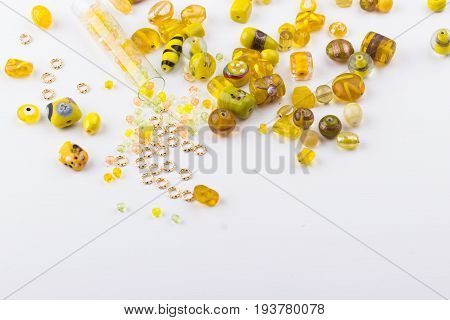 Yellow and lime glass bead mix on white background. Selective focus. Top view.