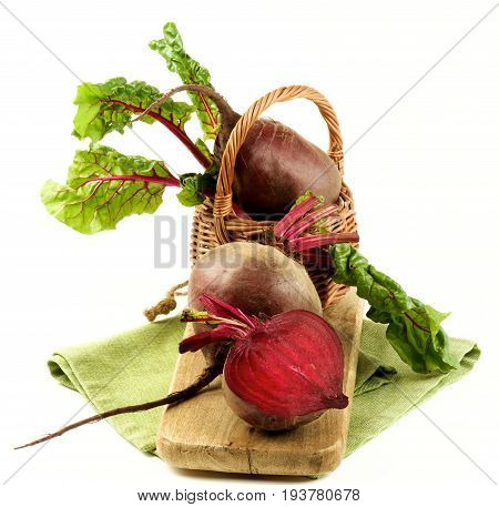 Fresh Raw Organic Beet Roots with Green Beet Tops Full Body and Half in Wicker Basket on Wooden Board and Napkin isolated on White background