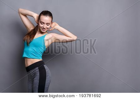 Beautiful fitness girl posing on gray studio background. Portrait of confident sporty woman with perfect body, healthy lifestyle and bodycare concept