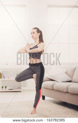 Yoga at home. Woman in tree pose, vrksasana. Young slim girl makes exercise near sofa