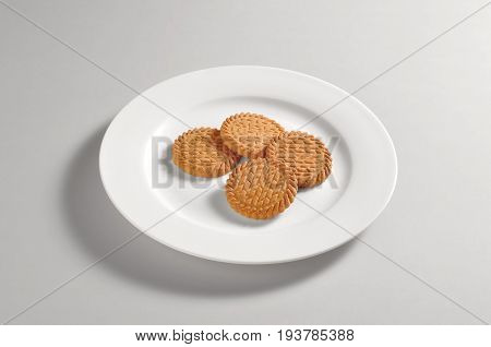 Round dish with 4 shortbread biscuits isolated on grey background