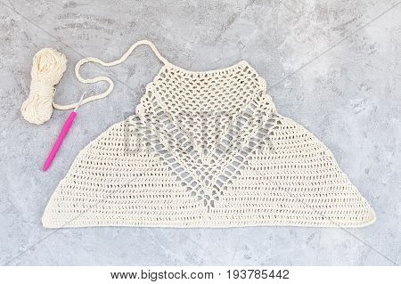 White crocheted crop top made of cotton on a gray background with crochet and thread