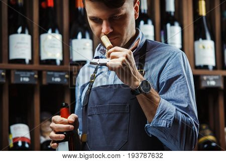 Sommelier smelling flavor of cork from red wine on background of shelves with bottles in cellar. Male appreciating quality of drink. Professional degustation expert in winemaking.