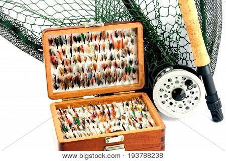 A fly fishing outfit of rod reel landing net and flies in wooden fly box on a white background