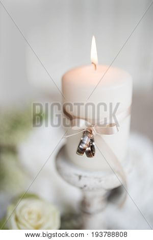 Burning candle with white loop and wedding rings in front of a tender background
