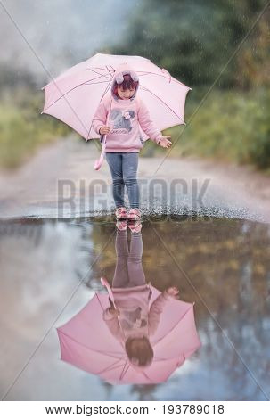 Girl with pink umbrella near puddle on rainy day