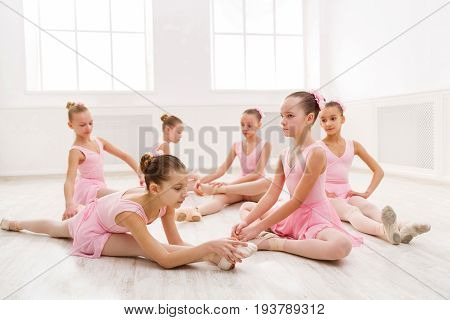 Young ballerinas stretching before performance, classical dance school