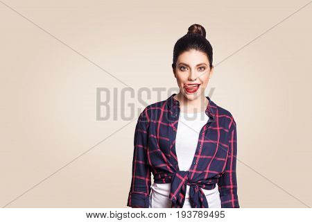 Portrait of attractive tempting woman with black bun hair touching licking her lips looking at camera with flirting and seductive eyes standing against beige copy space wall background.