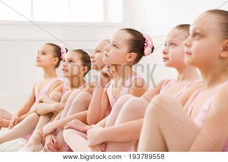 Little ballerinas in ballet studio. Group of girls having break in practice, sitting on floor. Classical dance school