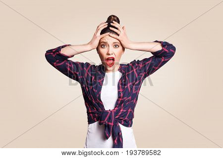 Portrait of hysterical Caucasian girl with bun hair looking in despair and panic being late for important exam or event not knowing what to do hands on her head mouth wide open. looking at camera.