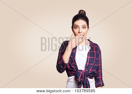 Portrait of young desperate woman in casual style amd bun hairstyle looking surprised with mouth wide open and hands. Female in despair and shock