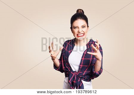 Portrait of stressed and annoyed young casual styled caucasian woman with hair bun holding hands in mad furious gesture screaming with ragea nd anger. Negative human emotions facial expressions