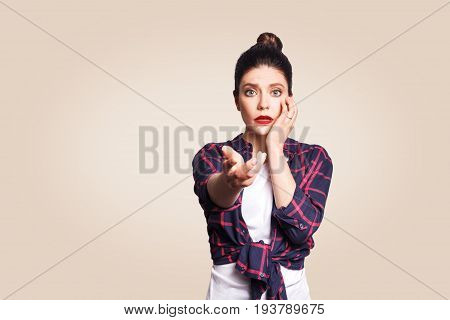 Scared girl with bun hair knot having scared and frightened look keeping mouth open touching face and pointing hand at camera.
