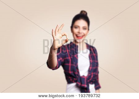 OK. Happy toothy smiley young woman showing OK sign with fingers. studio shot on beige background. focus on hand.