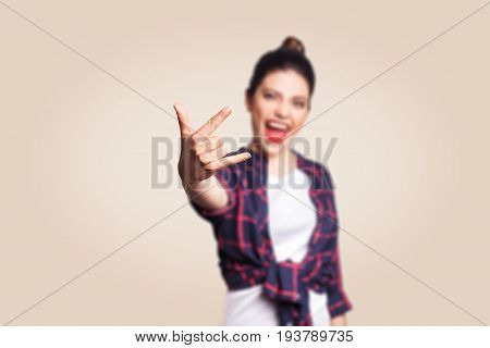 Rock sign. Happy funny toothy smiley young woman showing Rock sign with fingers. studio shot on beige background. focus on fingers.