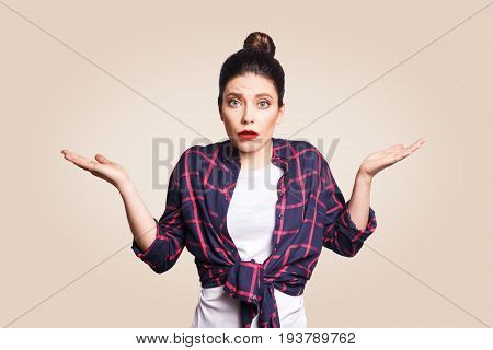 Portrait of young shocked brunette woman with casual style looking desperate or panic keeping mouth open and making helpless gesture with her hands doesn't know what to do.