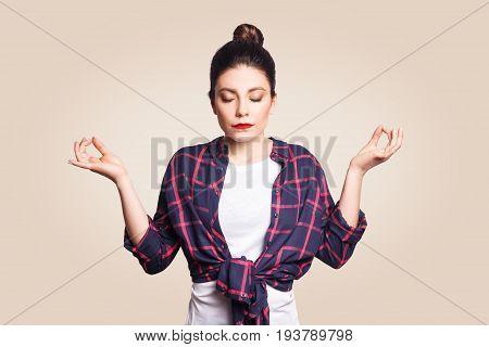 Meditation religion and spiritual practises. Beautiful young brunette girl doing yoga in the morning indoors at beige wall after waking up keeping eyes closed holding fingers in mudra gesture