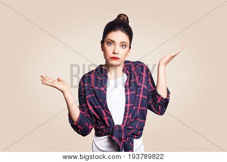 Puzzled and clueless young woman with arms out shrugging her shoulders saying: who cares so what I don't know. Negative human emotions facial expressions life perception and attitude.