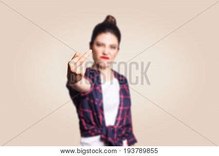 Middle finger sign. Unhappy angry young woman showing middle finger with unsatisfied face. studio shot on beige background. focus on fingers.