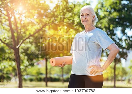 Full of gladness. Cheerful aged woman holding joga carpet and smiling while doing exercises in the park