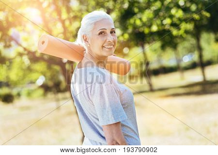 Best way to relax. Positive contented senior woman holding yoga carpet and expressing gladness while standing in the park