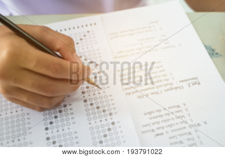 Blurred of student testing english exam or exercise on exams answer sheets with pencil in class room at high school or college education concept