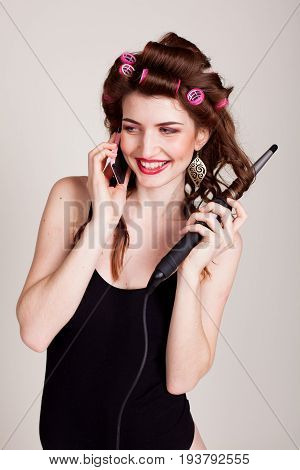 girl with hair curlers talking on the phone and makes the hairstyle