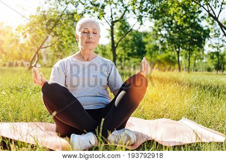 Peaceful state of mind. Pleasant delighted aged woman preactiving yoga in the park and closing her eyes while enjoying time