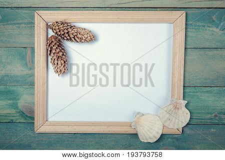 Blank photo frame with pine cones and sea shells on wooden background