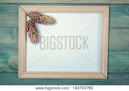 Blank photo frame with two pine cones on wooden background