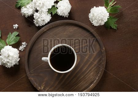 Morning cup of black coffee with flowers of viburnum. View from above.