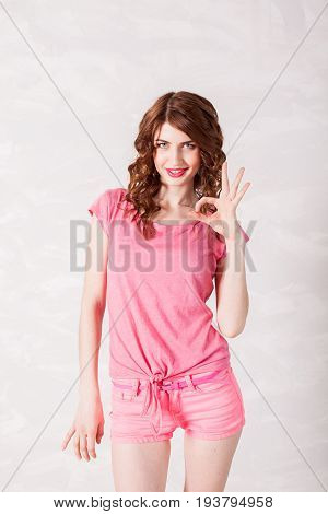 girl pinup style in a pink dress shows symbols with their hands