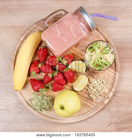 Detox cleanse drink, fruits and berries smoothie ingredients. Natural, organic healthy juice for weight loss diet or fasting day. Mason jar of dietary drink with strawberries, microgreens and banana.