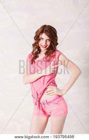girl pinup style in a pink dress shows 2 fingers