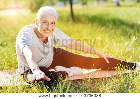 Likie what you do. Overjoyed smiling senior woman stretching and sitting on the roll mat while doing sport exercises in the park
