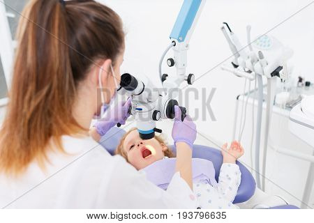 Female pediatric doctor examining mouth of little adorable patient girl with magnifying glass in a hospital. Dentist and child in cabinet. Dentist office. Little girl sitting in the dentists office