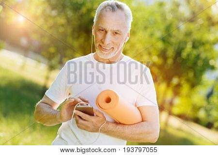 Music lover. Cheerful handsome aged man holding roll mat and listening to music while standing in the park